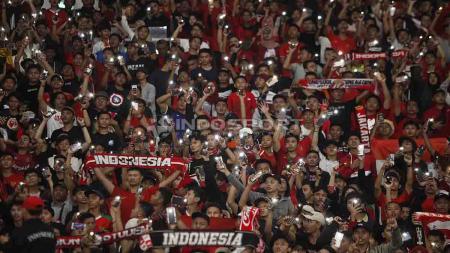 Aksi suporter menyalakan flash light di laga uji coba Timnas Indonesia Senior melawan Vanuatu di Stadion Utama Gelora Bung Karno, Sabtu (15/06/19). Foto Herry Ibrahim - INDOSPORT