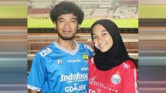 Indosport - Salah satu suproter Timnas Indonesia, Badu bersama istrinya tampak mengenakan jersey Persib dan Persija saat menyaksikan Timnas Indonesia vs Vanuatu
