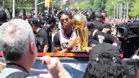 Salah satu pemain Toronto Raptors tengah membawa trofi di parade juara NBA 2019.