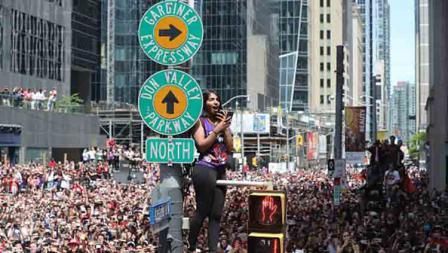 Salah satu wanita naik tiang marka jalan di acara parade Toronto Raptors.