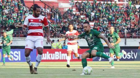Pemain Persebaya, Damian Lizio saat dihadang oleh pemain Madura United pada Piala Indonesia di Stadion Gelora Bung Tomo, Rabu (19/06/2019). Foto: Fitra Herdian/INDOSPORT - INDOSPORT