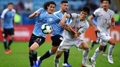 Indosport - Edinson Cavani dan Takehiro Tomiyasu  di laga Uruguay vs Jepang pada turnamen Copa America 2019, Jumat (21/06/19)