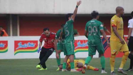 Pemain PSS Sleman berusaha memanggil tim media untuk membantu Indra Kahfi. - INDOSPORT