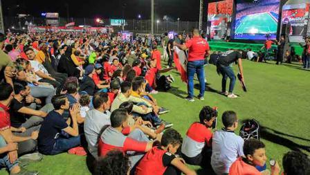 Masyarakat Mesir menyaksikan laga pembukan Piala Afrika Mesir vs Zimbabwe di layar besar luar stadion.