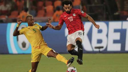Mohamed Salah berusaha melewati jegalan dari Divine Lunga di Cairo International Stadium, Sabtu (22/06/19).