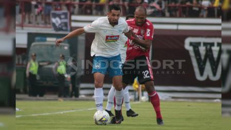 Silvio Escobarsaat dikawal ketat bek Bali United, Leonard Tupamahu dalam pertandingan di Stadion Kapten I Wayan Dipta, Gianyar, Sabtu (22/6/2019) sore. INDOSPORT/Nofik Lukman Hakim - INDOSPORT
