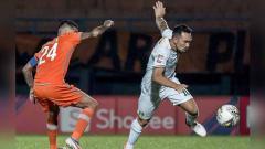 Indosport - Diego Michiels (kiri) membayangi pergerakan Damian Lizio yang menguasai bola, Minggu (23/06/2019).