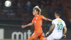 Indosport - Asri Akbar (kiri) mencoba menguasai bola saat dibayang-bayangi Manucekhr Jalilov, Minggu (23/06/2019).