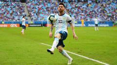 Indosport - Lionel Messi mengontrol bola pada laga melawan Qatar di Arena do Gremio.