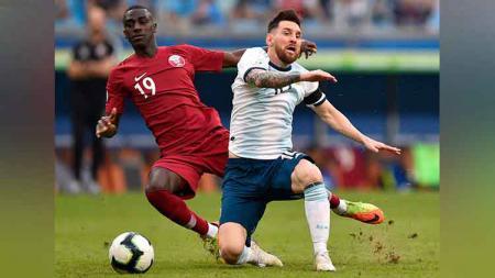 Lionel Messi gagal  membawa bola setelah mendapat jegalan dari Almoez Ali. - INDOSPORT