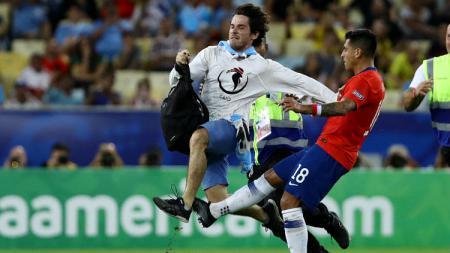 Pemain Chile Gonzalo Jara, menekel seorang pitch invader dalam laga melawan Uruguay di Copa America, Selasa (25/06/19). - INDOSPORT