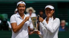 Indosport - Tami Grende dan Qiu Yu Ye, memegang trofi girls doubles di Wimbledon 2014.
