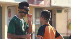 Indosport - Otavio Dutra berbincang dengan dokter Persebaya mengenai maskernya saat latihan di Lapangan Polda Jatim, Selasa (25/6/19).
