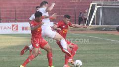Indosport - Salah satu pemain Bali United memaksa untuk merebut bola dari dua pemain Kalteng.