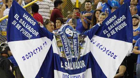 Salah seorang fans El Salvador menutup badannya dengan kostum negaranya di Cuscatlan Stadium (23/03/19). Alex Pena/Getty Images - INDOSPORT