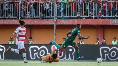 Striker Amido Balde dihalau kiper Muhammad Ridho pada laga Madura United vs Persebaya Surabaya di Kratingdaeng Piala Indonesia 2018/2019, Kamis (27/06/19). - INDOSPORT