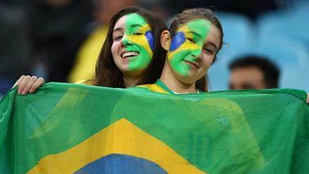 Dua suporter cantik Timnas Brasil memberikan sanyuman manisnya sambil bentangkan bendera kebangsaan mereka di Arena do Gremio, Jumat (28/06/19).
