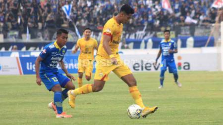 Bek Bhayangkara FC, Jajang Mulyana, saat berebut bola dengan pemain Persib, Febri Hariyadi, Minggu (30/06/2019). Foto: Arif Rahman/INDOSPORT - INDOSPORT