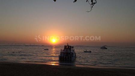 Sebuah kapal yang akan mengangkut wisatawan menuju Nusa Penida, dengan background sunrise. Foto : Nofik Lukman Hakim - INDOSPORT