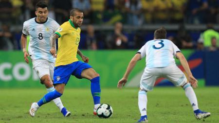 Dani Alves menggiring bola sambil dikawal ketat oleh pemain Argentina. - INDOSPORT