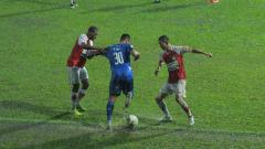 Indosport - M. Rafli (tengah) lebih keras membawa bola akibat hujan deras di laga Arema FC vs Persipura Jayapura