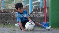 Indosport - Roma saat bermain di pinggir lapangan, menanti sang ayah yang sedang melatih Bali United, Kamis (04/07/19)