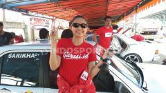 Indosport - Pembalap wanita, Sarikha Kartika Ayu berpose di depan mobilnya.