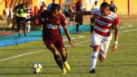 Pergerakan sayap PSM Makassar, Zulham Zamrun (kiri) mendapatkan pengawalan ketat dari bek Madura United, Jaimerson Xavier. - INDOSPORT