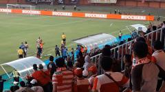 Indosport - Suporter Madura United lempar botol ke lapangan.