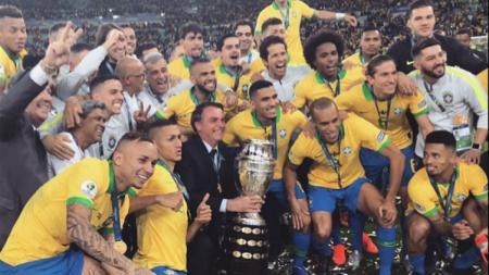 Presiden Brasil, Jair Bolsonaro, merayakan gelar Copa America 2019 negaranya usai mengalahkan Peru pada hari Senin (08/07/19) - INDOSPORT