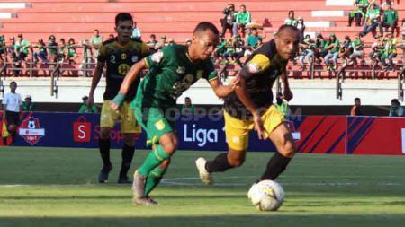 Irfan Jaya duel dengan salah satu pemain Barito Putera di Stadion GBT. - INDOSPORT