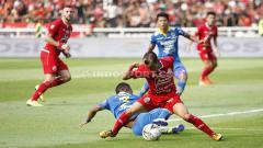 Indosport - Riko Simanjuntak merebut bola dari pemain Persib.