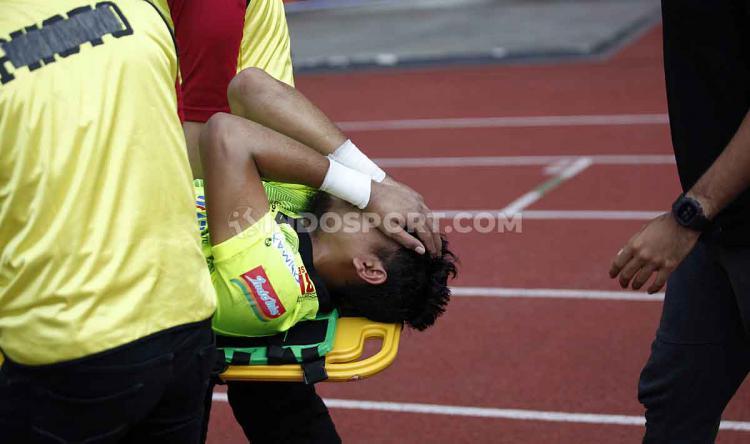 Natshir Mahbuby terkapar dibawa keluar lapangan untuk ditangani tim medis. Copyright: Herry Ibrahim/INDOSPORT