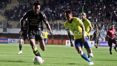 Bek PSS Sleman, Ikhwan Ciptadi saat berebut bola dengan striker Barito Putera di ajang Piala Indonesia. Foto: Ronald Seger Prabowo/INDOSPORT - INDOSPORT