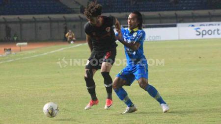 Pemain Persib Bandung, Hariono mencoba merebut bola dari pemain Kalteng Putra pada pertandingan Shopee Liga 1 2019 di Stadion Si Jalak Harupat, Kabupaten Bandung, Selasa (16/07/2019). Foto: Arif Rahman/INDOSPORT - INDOSPORT