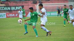 Indosport - Pemain PSMS Medan, Ilham Fathoni (kiri baju hijau) diapit pemain pemain bertahan Blitar United, Fafa Muhammad Zuhud (kanan baju putih). Foto: Aldi Aulia Anwar/INDOSPORT