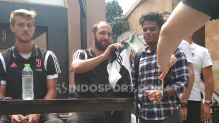 Gonzalo Higuain tersenyum ketika wartawan INDOSPORT memanggilnya saat sedang memberi tanda tangan pada fans Juventus. - INDOSPORT