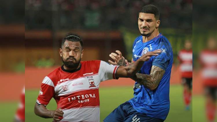 Fandry Imbiri (kiri) dikawal Arthur Cunha (kanan) pada laga Madura United vs Arema FC di Stadion Gelora Ratu Pamelingan dalam lanjutan pekan ke-10 Liga 1 2019, Sabtu (20/07/19). Copyright: Instagram/@aremafcofficial