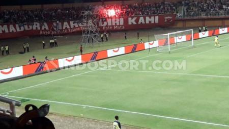 Suporter Madura United menyalakan flare sehingga berbuah ancaman sanksi komdis - INDOSPORT