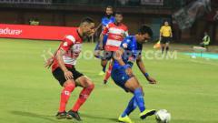 Indosport - Striker Arema FC, Dedik Setiawan (kanan) dikawal ketat bek Madura United, Jaimerson