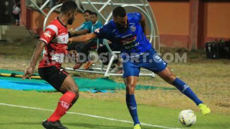 Perebutan bola antara pemain Arema FC, Sylvano Comvalius (kanan) dengan pemain Madura United, Marko Merauje. - INDOSPORT