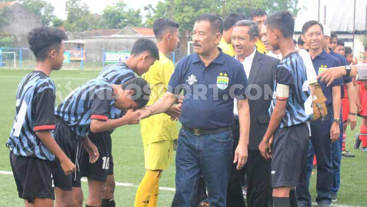 Manajer Persib, Umuh Muchtar bersalaman dengan pemain yang mengikuti kompetisi  Piala H Umuh Muchtar U-15  di Lapangan Lodaya. Copyright: Arif Rahman/INDOSPORT