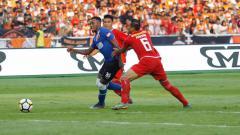 Indosport - Guy Junior (biru) melewati hadangan bek Persija Jakarta, Maman Abdurahman