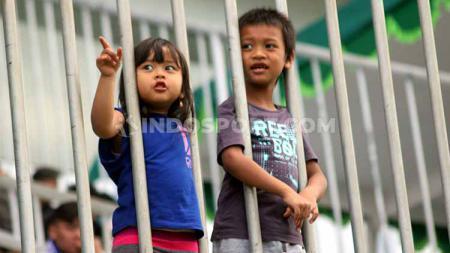 Dua orang anak asyik menyaksikan laga PSS Sleman melawan PSIS Semarang di Stadion Maguwoharjo, pekan lalu - INDOSPORT