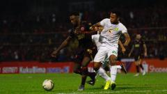 Indosport - Penyerang PSM Makassar, Guy Junior (merah) berduel dengan bek Persebaya Surabaya, Otavio Dutra (putih).