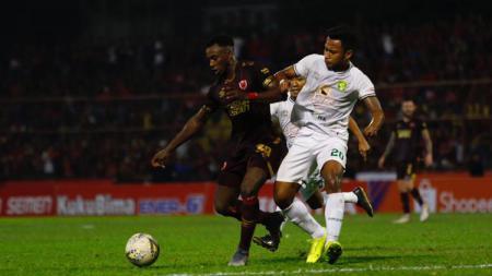 Penyerang PSM Makassar, Guy Junior (merah) berduel dengan bek Persebaya Surabaya, Otavio Dutra (putih). - INDOSPORT