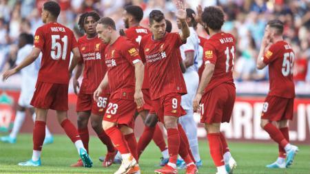 Seorang penggemar cilik Liverpool nekat melompat pagar pembatas dan menerobos masuk lapangan demi berburu kaos pemain Liverpool. - INDOSPORT