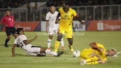 Indosport - Herman Dzumafo berusaha keras merebut bola dari pemain Madura United di Liga 1 di Stadion Madya Senayan, Senin (05/08/19).