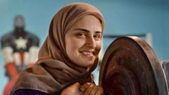Indosport - Kulsoom Abdullah, atlet angkat besi berhijab yang juga bergelar doktor. Foto: Associated Press.