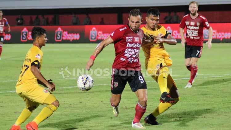 Dua pemain Semen Padang menghalau Spasojevic untuk merebut bola. Copyright: Nofik Lukman Hakim/INDOSPORT